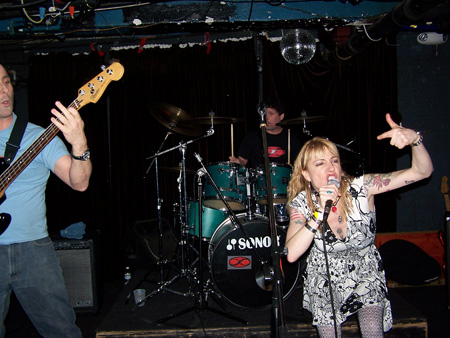 Kevin, Kerry and Cindy Lou playing live at Blakes in Berkeley. Kevin on left playing bass, Kerry on drums in center, and Cindy Lou leaning over singing into mic with left hand raised with thumb up and index finger pointing at herself