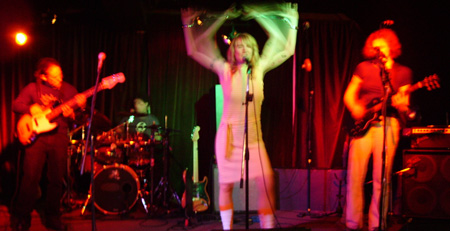 Mobius Donut live in San Francisco. Kevin playing bass on the left, Cindy Lou in the center waving her arms with blurry/multiple arms effect, and Andrea playing guitar on the right under red light