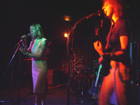 Andrea and Cindy Lou on stage live in San Francisco. Andrea on the right playing guitar in red light, and Cindy Lou singing into mic under purple light