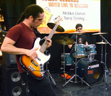 Kevin and Kerry playing live at Tower Records. Kevin on the left looking down and playing bass. Kerry in the background playing drums