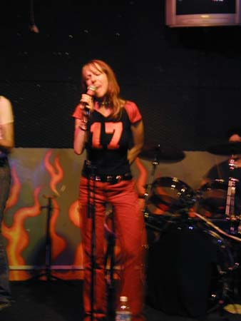 Cindy Lou on stage live in San Francisco under red light holding a mic