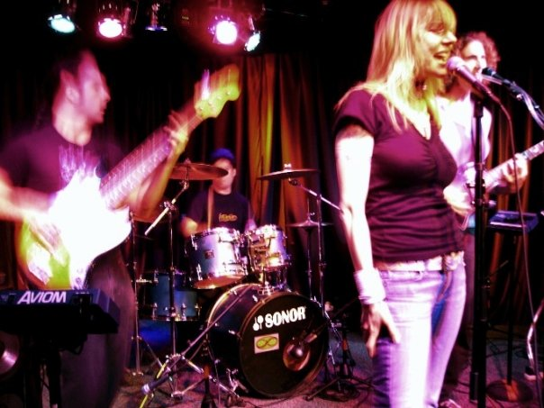Mobius Donut on stage in Walnut Creek. Kevin on the left blurred, Kerry on drums in the background, Cindy Lou and Andrea on the right