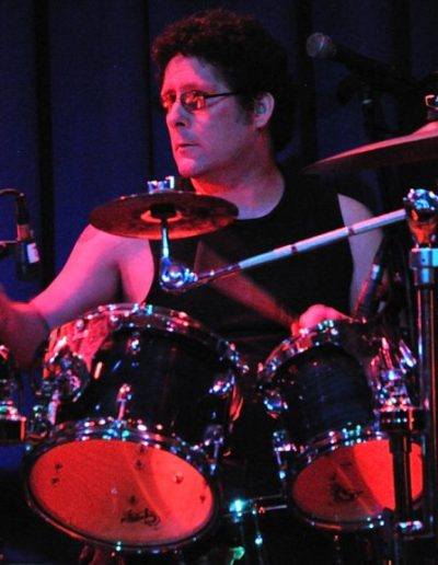Kerry Stamps playing drums under red light against a dark blue background